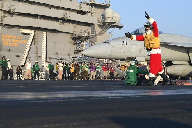 Lt. Larry Young, dressed as Santa, signals an F/A-18 E Super Hornet, assigned to the Stingers of Strike Fighter Attack Squadron (VFA) 113 on the flight deck of the aircraft carrier USS Theodore Roosevelt (CVN 71) Dec. 21, 2017