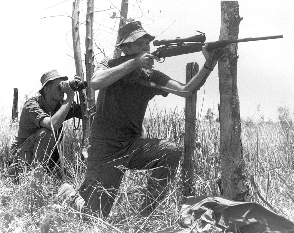 """Marine sniper, PFC D. M. Taylor, sights-in on an enemy NVA rifleman harassing Marines during an operation south of Phu Bai. Cpl Bruce V. MacDonald helps the shooter to locate enemy troops. August 15 1967."" (Photo/caption: U.S. Marine Corps History Division)"