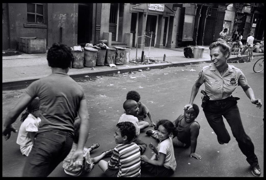 """New York City police officer plays with kids in Harlem, 1978."" Note the 38 sw"