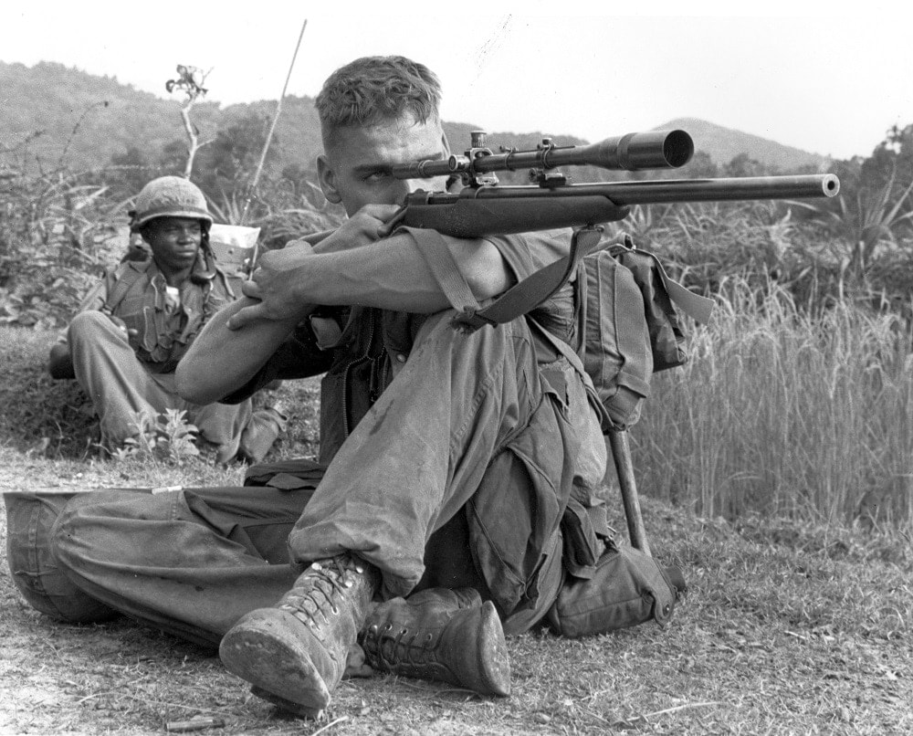 """OPERATION VIRGINIA- -Marine Lance Corporal Dalton Gunderson checking the area for Viet Cong snipers, 1966"" Note the Unertl-equipped rifle. (Photo/caption: U.S. Marine Corps History Division)"
