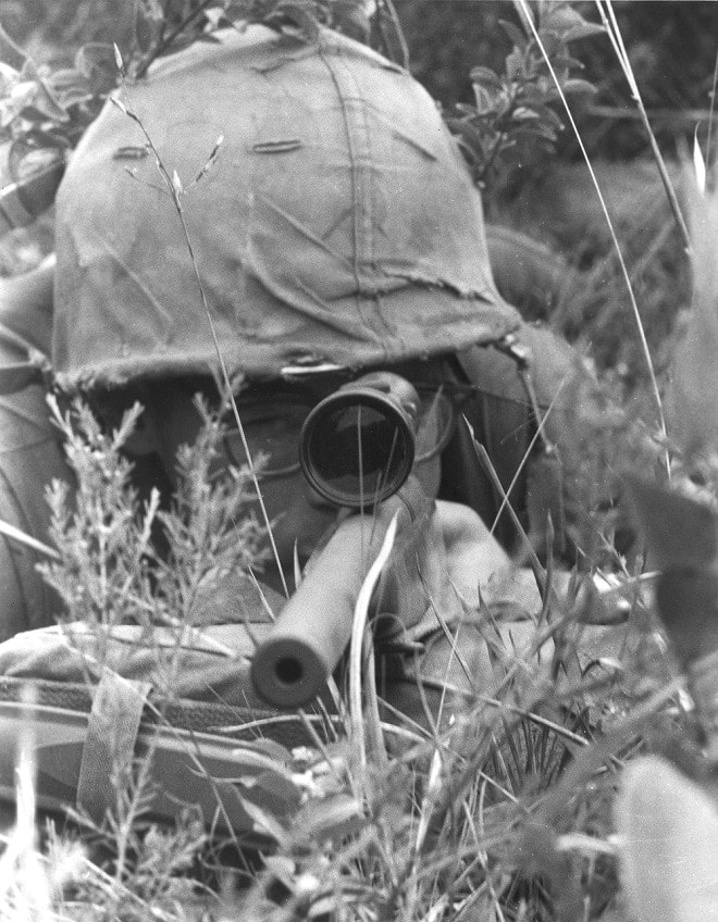 """Pvt. Randall E. Josey, a Marine sniper attached to Co. H, 2nd Bn., 5th Marines, has a bead on a Viet Cong at over 1,000 meters. Using a 3 x 9 power scope, a Remington 700 rifle has accuracy up to 1,100 meters and has been used effectively up to 2,000 meters or more."" June 19 1967 (Photo/caption: U.S. Marine Corps History Division)"
