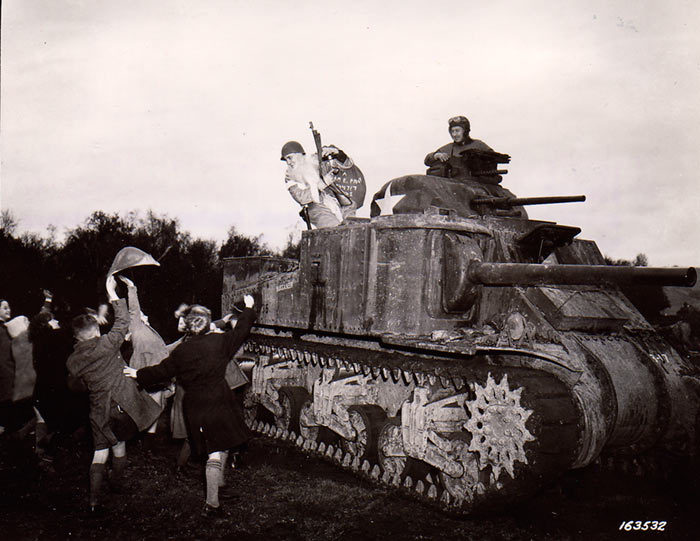 """""""Sergeant plays Santa for British children during WWII, 1942."""" Note the Thompson submachine gun and Grant tank"""