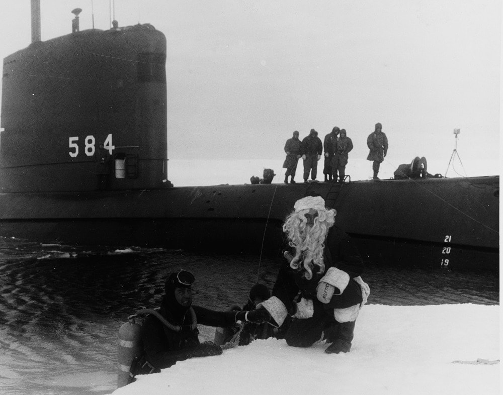 """USS SEADRAGON (SSN-584) Caption """"Frogman Lieutenant G.M. Brewer is greeted by Santa Claus, the mayor of the North Pole, during the ship's polar cruise, September 1960."""" (Photo: U.S. Navy)"""