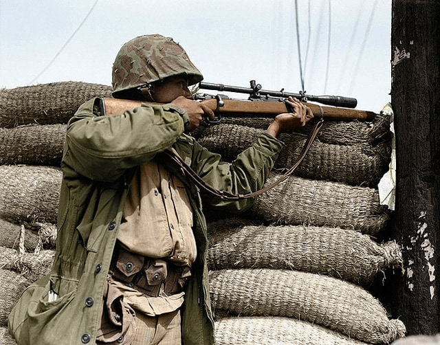 A U.S. Marine Marksman using a telescopic sight and with his Springfield cocked and ready, waits for a troublesome North Korean sniper to pop up so he can pick him off in Seoul, capital city of South Korea on Sept. 28, 1950. (AP Photo/Max Desfor