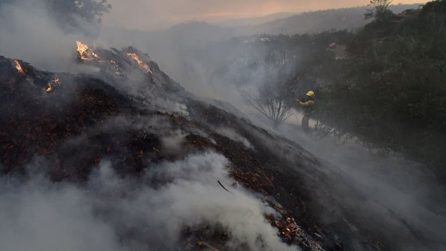 A firefighter puts out hotspots on a smoldering hillside in Montecito, California as strong winds blow smoke and embers inland, Dec. 16, 2017 at the Thomas Fire. (Photo: Robyn Beck/AFP/Getty Images)