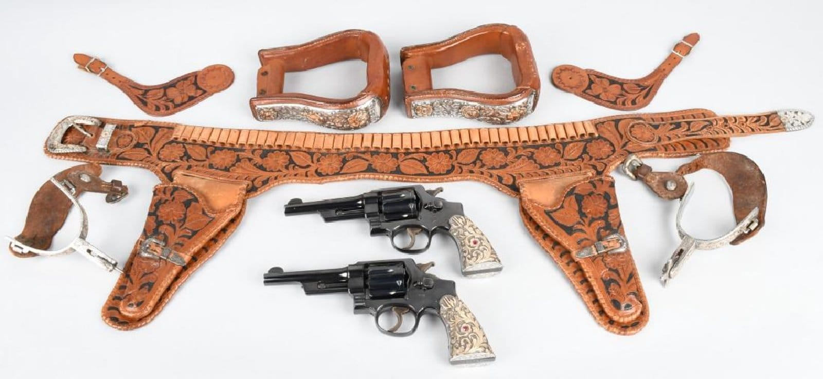 Two 1932 Smith & Wesson matching .38/.44 fixed-sight revolvers, personal property of movie icon John Wayne, JW initials on grips, hand-tooled leather double holster with gold-overlaid, ruby-adorned silver buckles; stirrups, spurs. Est. $10,000-$20,000. (Photo: Milestone Auctions)