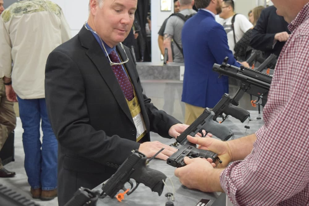 A Heckler & Koch rep at the HK booth showing an HK pistol with Crimson Trace kit to a potential client. (Photo: Daniel Terrill/Guns.com)