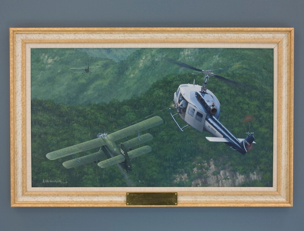 """""""An Air Combat First"""" painting by Keith Woodcock in the CIA's collecton remembers the occasion that an Air America helicopter fought off at attack on a remote radar site just over the North Vietnamese border with Laos. (Photo: CIA)"""