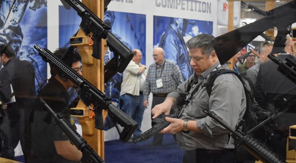 A patron checking out a new rifle at the Rock River Arms booth during SHOT Show 2018. (Photo: Daniel Terrill/Guns.com)
