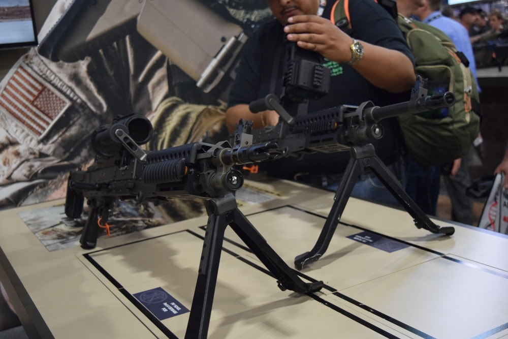 A patron toying around with an FN machine gun -- unloaded and decommissioned -- during SHOT Show 2018. (Photo: Daniel Terrill/Guns.com)