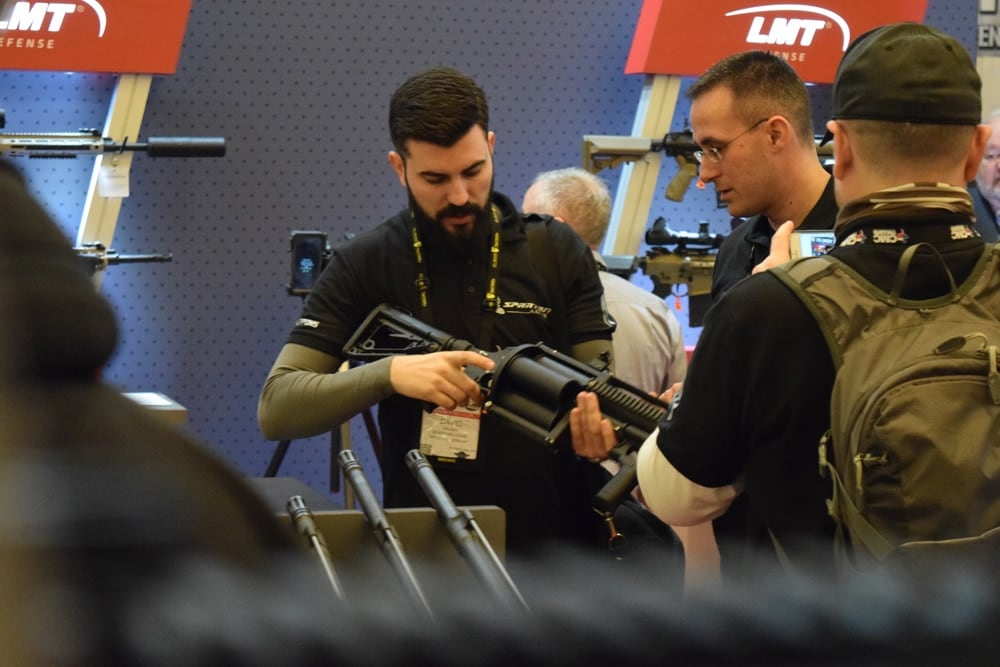 An LMT rep shows a patron how to work the grenade launcher at SHOT Show 2018 in Las Vegas. (Photo: Daniel Terrill/Guns.com)