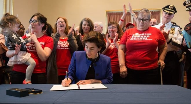 "Gov. Gina Raimondo, among a crowd of gun control advocates, signed an executive order this week focusing on removing guns from some in so-called ""red flag"" cases. (Photo: Governor's office)"