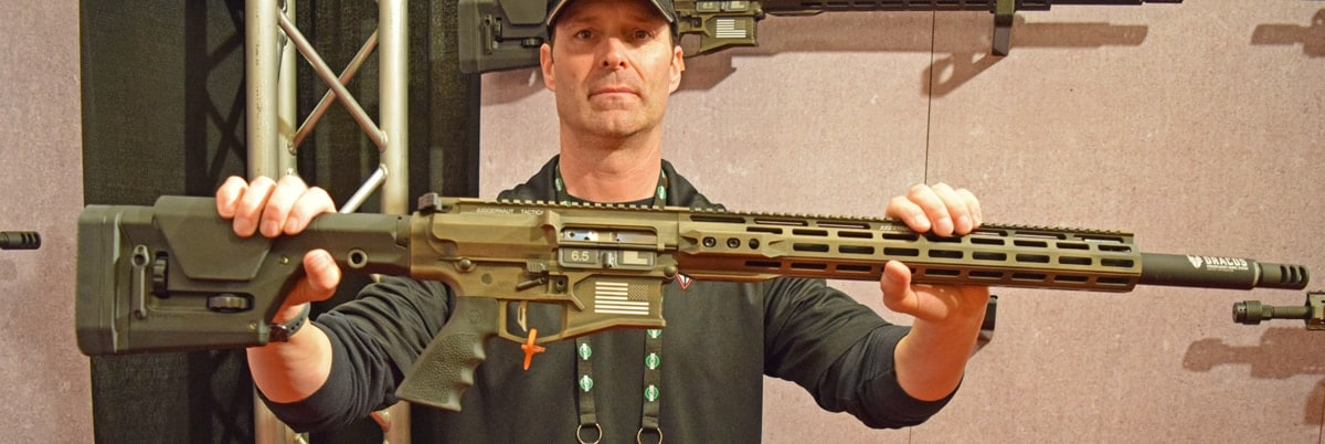 Juggernaut representative Robert Griffin holds out the new Precision Rifle in 6.5 Creedmoor at the company's booth at SHOT Show 2018 in Las Vegas. The rifle had ambidextrous controls and is equipped with Magpul PRS Stock and anti-walking pins. (Photo: Daniel Terrill/Guns.com)