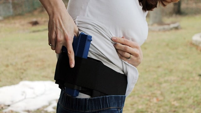 woman pulling a gun out of the crossbreed modular belly ban holster