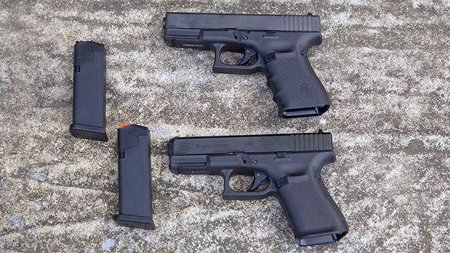 a glock 19 gen 5 and a glock 19 gen 5 sitting on a rock surface with magazines out