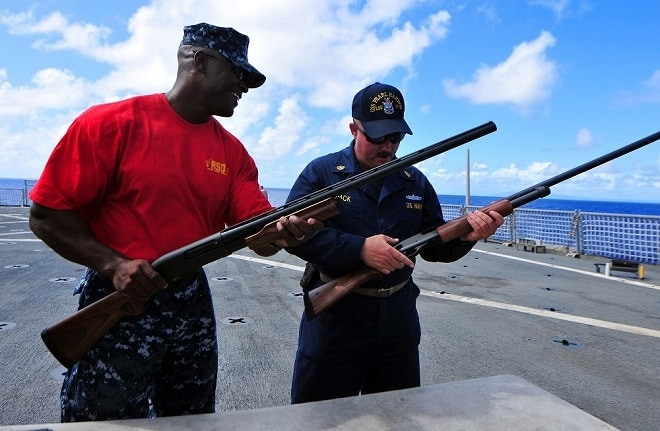 U.S. Navy Senior Chief Master-at-Arms Robert Goode, left, and Chief Gunner?s Mate Blair Pack inspect 12-gauge shotguns during a Navy Morale, Welfare and Recreation program skeet shoot on the flight deck of the amphibious dock landing ship USS Pearl Harbor (LSD 52) Nov. 28, 2010. Pearl Harbor is part of the Peleliu Amphibious Ready Group and was in the Mariana Straits while transiting the U.S. 7th Fleet area of responsibility. (DoD photo by Mass Communication Specialist 2nd Class Michael Russell, U.S. Navy/Released)