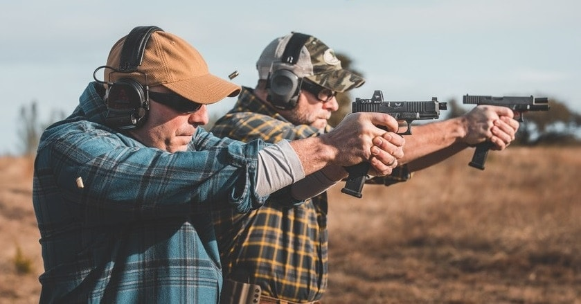 2 men shooting glocks outdoors with mag extensions