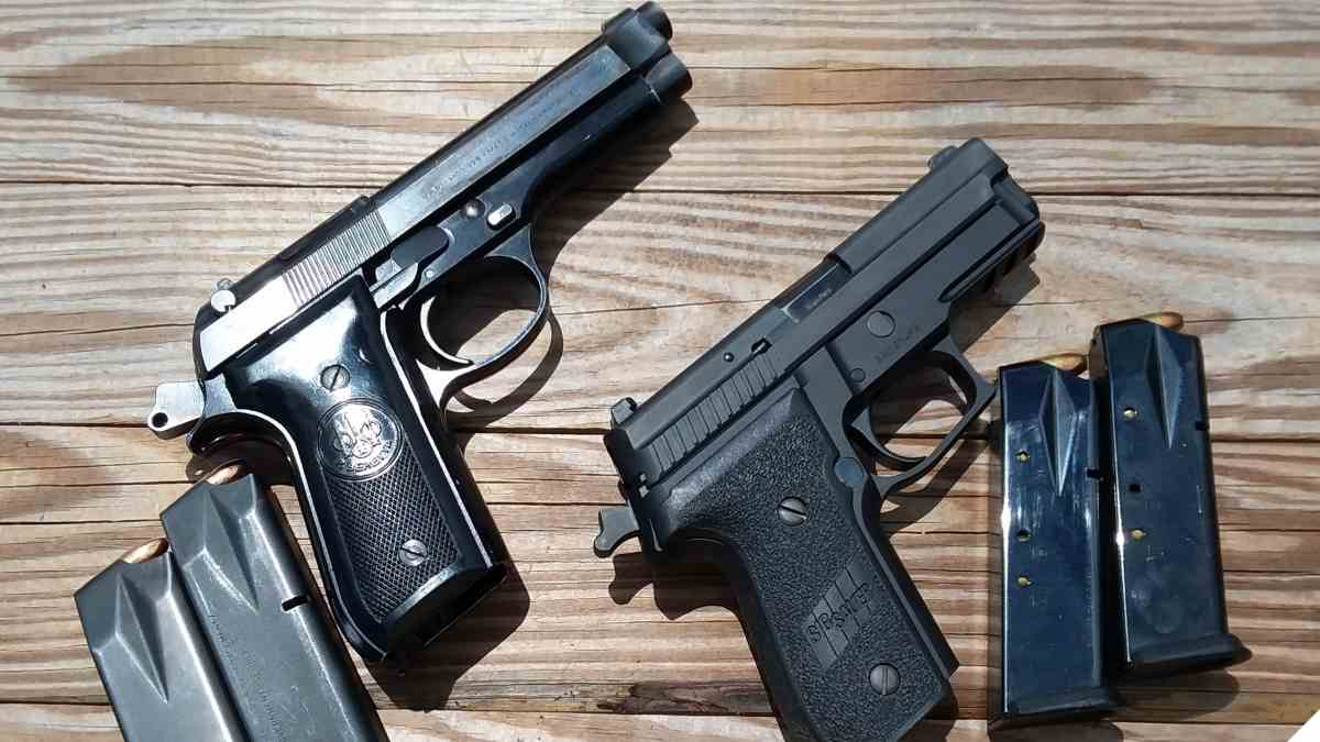 Sig P229 and Beretta 92 pistols on table