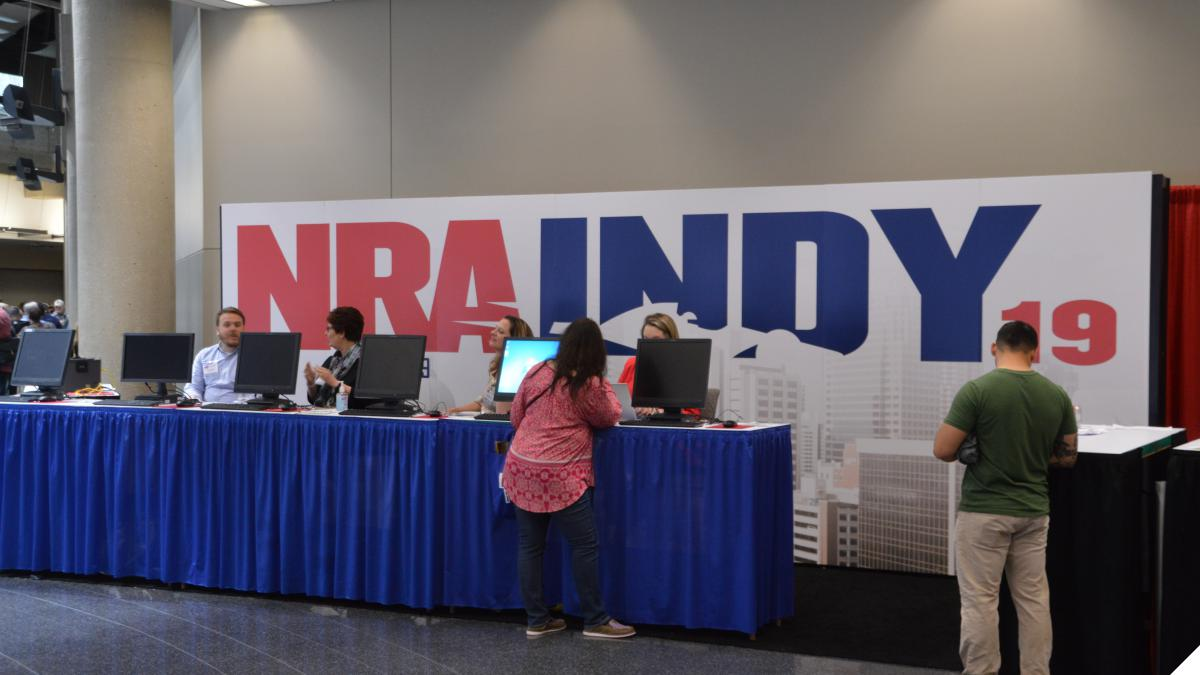 NRA Indy 19 sign with people waiting to sign up