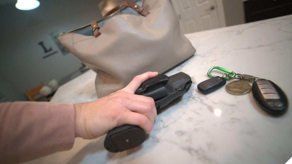 A woman grabs a Beretta APX carry off a kitchen counter near a purse