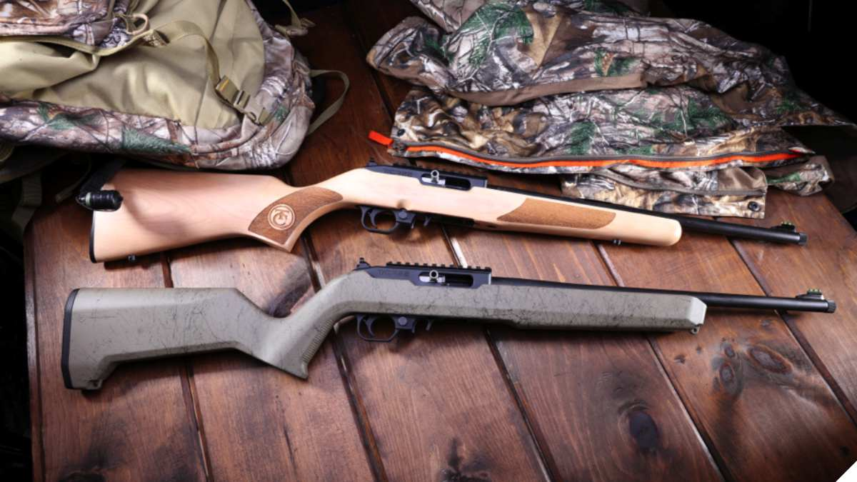 two tcr22 rifles next to hunting gear on a wood table