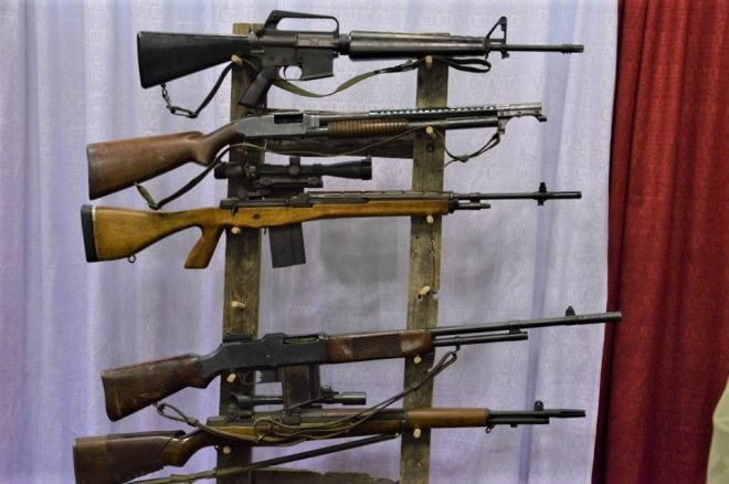 A cross-section of US military rifles and shotguns from the 1950s and 60s including an M14A1 with a full pistol grip and scope.
