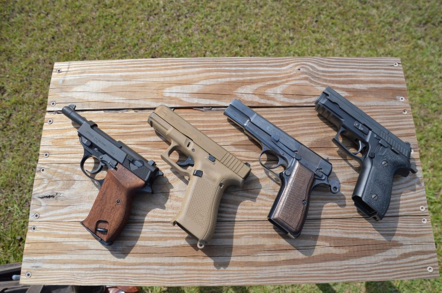 Sig P229 on a table with other guns