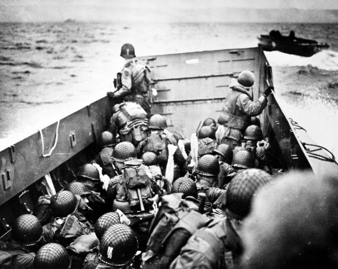 Troops crouch inside a LCVP landing craft, just before landing on Omaha Beach on D-Day, 6 June 1944. guns wrapped National Archives 26-G-2340