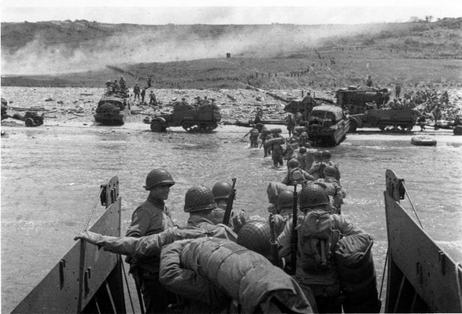 Troops wade ashore from a LCVP landing craft, off Omaha Beach, 6 June 1944 DUKWs and half-tracks at the water lineM1903 and M1 rifles carried by some of the troops leaving the landing craft SC 320902