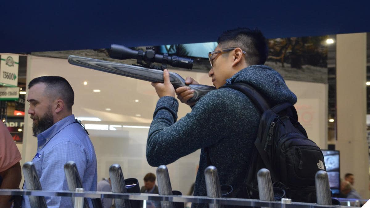 Man pointing a rifle scope
