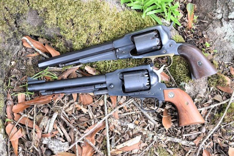"The top revolver is a circa 1865 martially-marked Remington New Army while the ""identical cousin"" below it is a 1999-produced Ruger Old Army. (Photo: Chris Eger/Guns.com)"