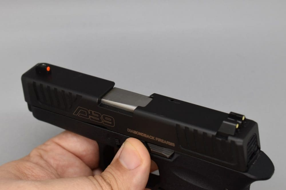 The replaceable sights include a red front post with green rear dots while night sights are readily available. Note the front and rear slide serrations and fenced slide stop lever