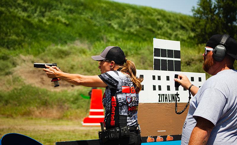 female in tactical team shirt shooting gun outdoor range