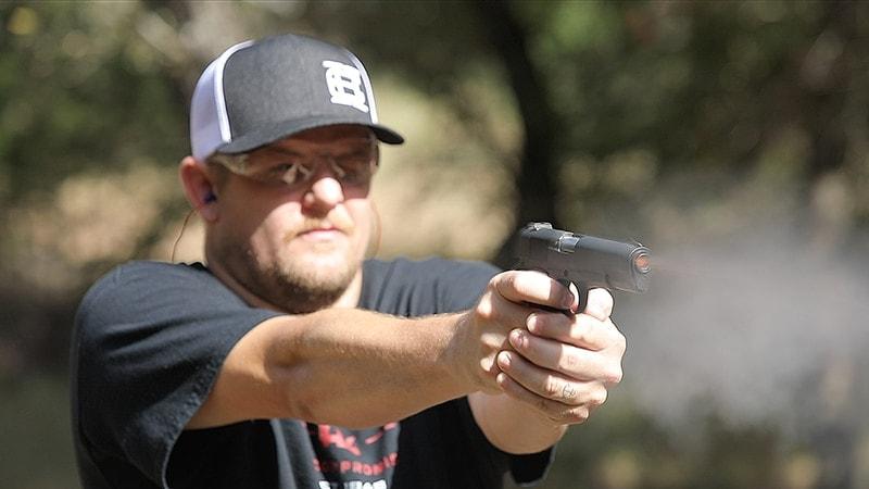 male shooting handgun outdoors at range