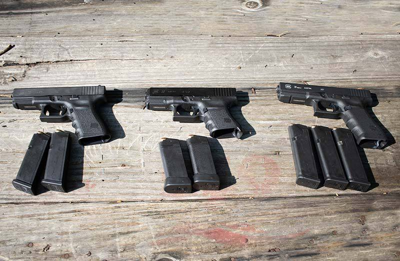 Glocks and their mags sitting on a wooden table for comparison