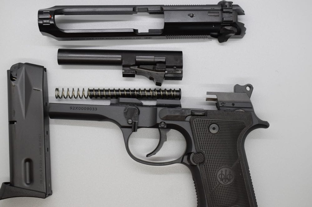 """The 92X series breaks down like any other Beretta 92 and does not require tools. Note the Gen 3 locking block on the barrel and oversized magazine release button. The so-called """"universal"""" slide allows the 92X's safety lever to be used in a safety/de-cocker mode (FS) or converted to a de-cocker-only (G) function by the user."""