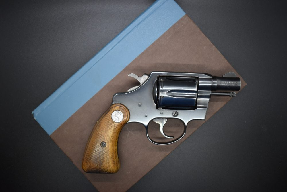 colt detective revolver sitting on top of a journal