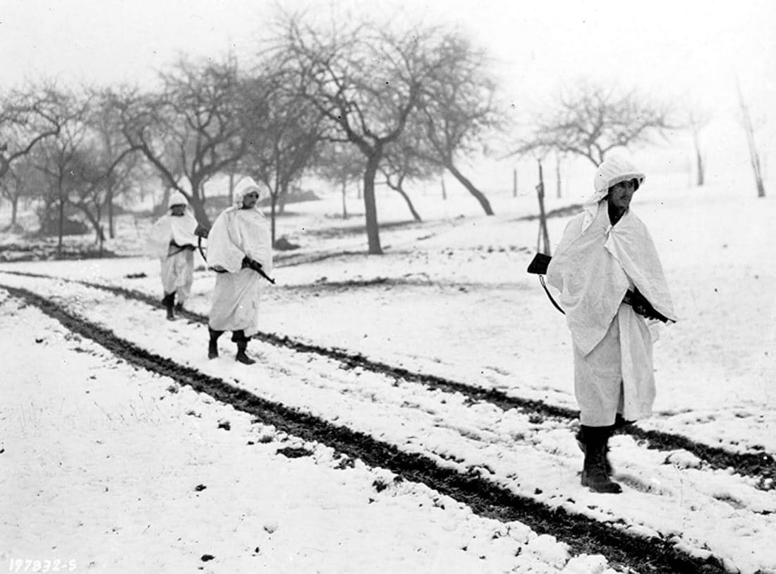 Three M1 Garand-armed members of an American patrol, Sgt. James Storey, of Newman, Ga., Pvt. Frank A. Fox, of Wilmington, Del., and Cpl. Dennis Lavanoha, of Harrisville, N.Y., cross a snow-covered Luxembourg field on a scouting mission in Lellig, Luxembourg, Dec. 30, 1944. White bedsheets camouflage them in the snow. (Photo: U.S. Army)