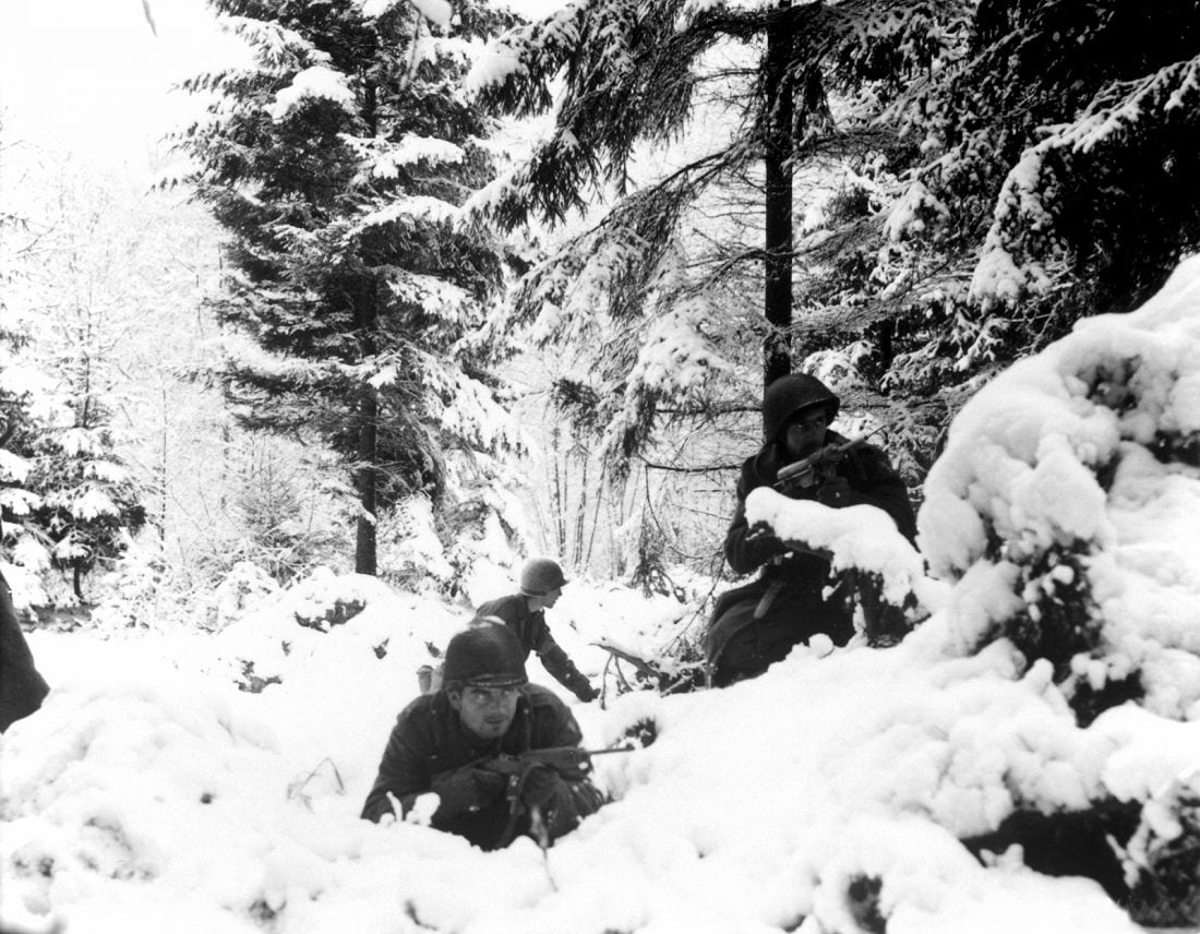U.S. Army infantrymen of the 290th Regiment, 75th Infantry Division, fight in fresh snowfall near Amonines, Belgium during the Battle of the Bulge, Jan. 4, 1945. Note the M3 Grease Gun to the right and M1 Carbine to the left. (Photo: U.S. Army)