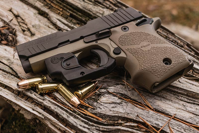 sig sauer p938 on rustic wood outdoors next to bullets