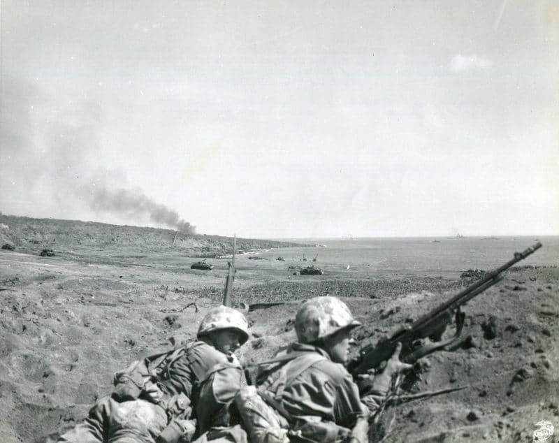 """""""FAITHFUL AND WAITING----While a gigantic artillery and tank battle rages behind them on the Iwo Jima beachhead, Marines (left to right) PFC Joseph de Blanc, of Union, Maine, and PFC Frank Hall, of Reed W. Virginia, faithfully wait for orders in a shell hole."""" Note the M1918 Browning Automatic Rifle (BAR)."""