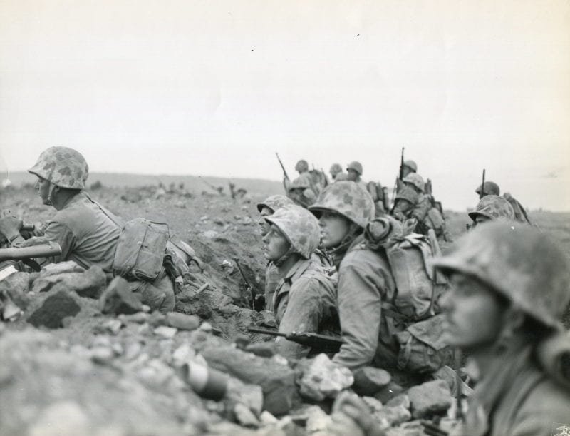"""""""FORMED---- Organized and formed for the assault, Marines of one of the Regiments of the Fourth Marine Division under Major General Clifton B. Cates, USMC, are ready to attack the enemy-held Motoyama Airfield Number One, on Iwo Jima, 500 yards inland from the beach."""" Note the Marines in the foreground with M1 Carbines and the unmistakable profile of M1 Garands in the distance."""
