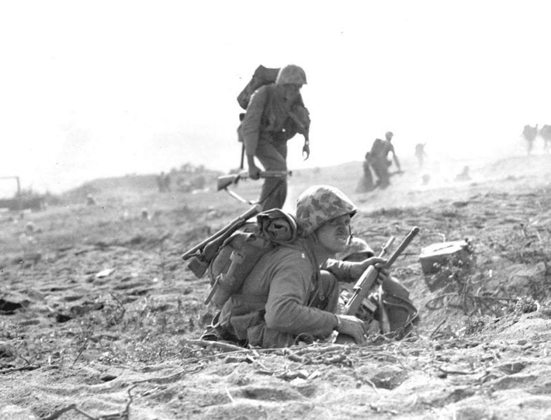 """""""GOING INLAND--- Determination written on their countenances, Marines start the drive to the interior of Iwo Jima. Running at a crouch, they dart across the table and in the shadow of Mount Suribachi, taking advantage of the scant protection offered by small rises in the volcanic sand."""" Note the M1 Carbine of the Marine in the foreground, with a rifle grenade attachment installed, and the Devil Dog with a Winchester Model 12 trench gun in the background."""