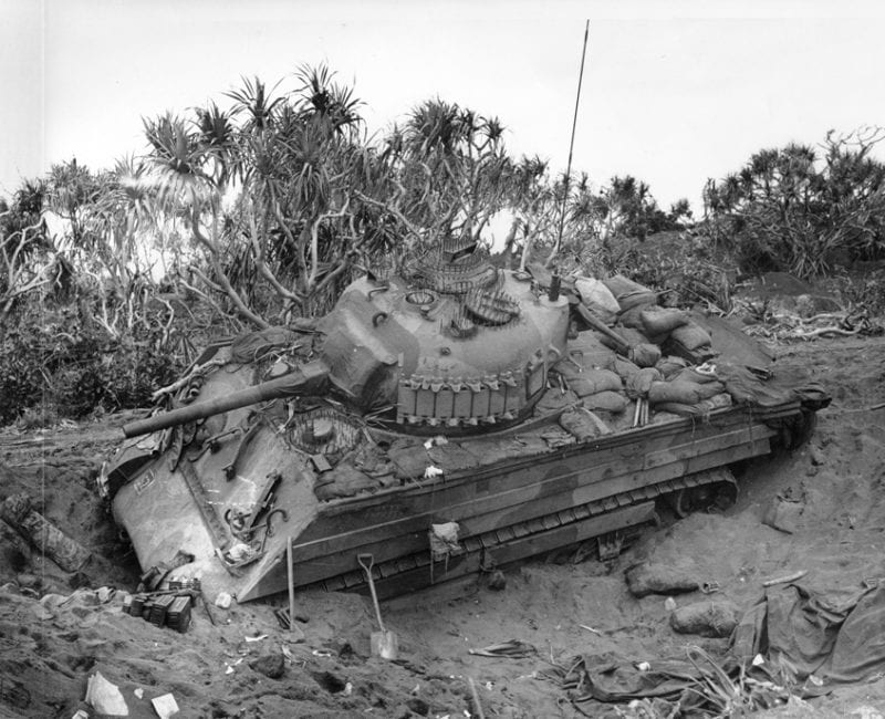 """Photo caption: """"Iwo Jima, February 21, 1945. Burrowed in the Sand: A Marine medium tank that couldn't navigate the soft volcanic sand on Iwo, is track deep in a pit off the beach. This loose sand of the island proved an asset to the Japanese defenders."""""""