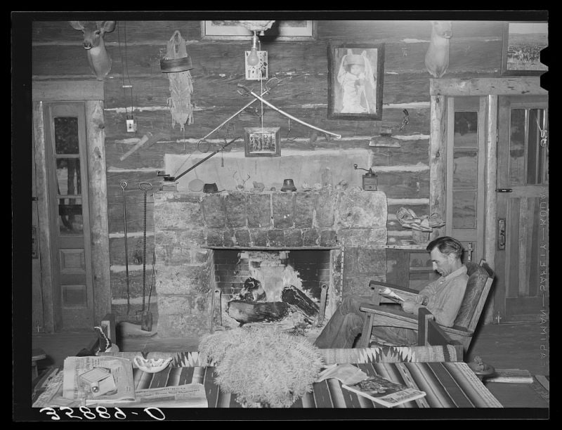 """Proprietor of the Navajo Lodge before the fireplace. Datil, New Mexico."" Note the crossed cavalry sabers on the wall and what looks like a S&W Lemon Squeezer top-break revolver."
