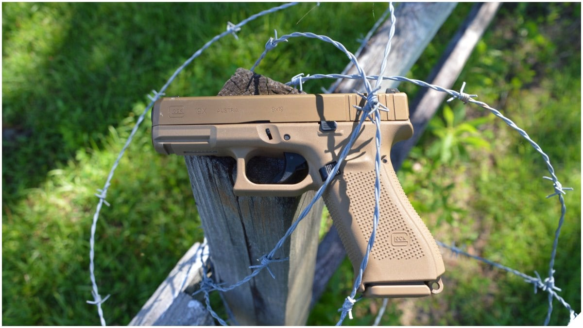 Glock G19X on a wooden fence encased in barbed wire
