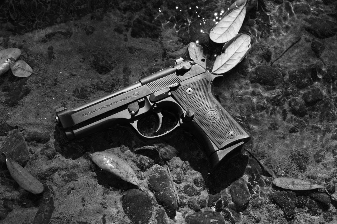 Beretta 92X Compact pistol in a rock bed stream shot in B&W short exposure with leaves floating by on a shallow, crystal clear swath of water about one-inch deep