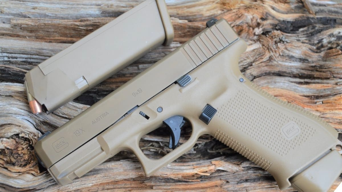 A Glock 19X resting on a wooden block with a 21-round magazine inserted and a 17-round magazine next to it