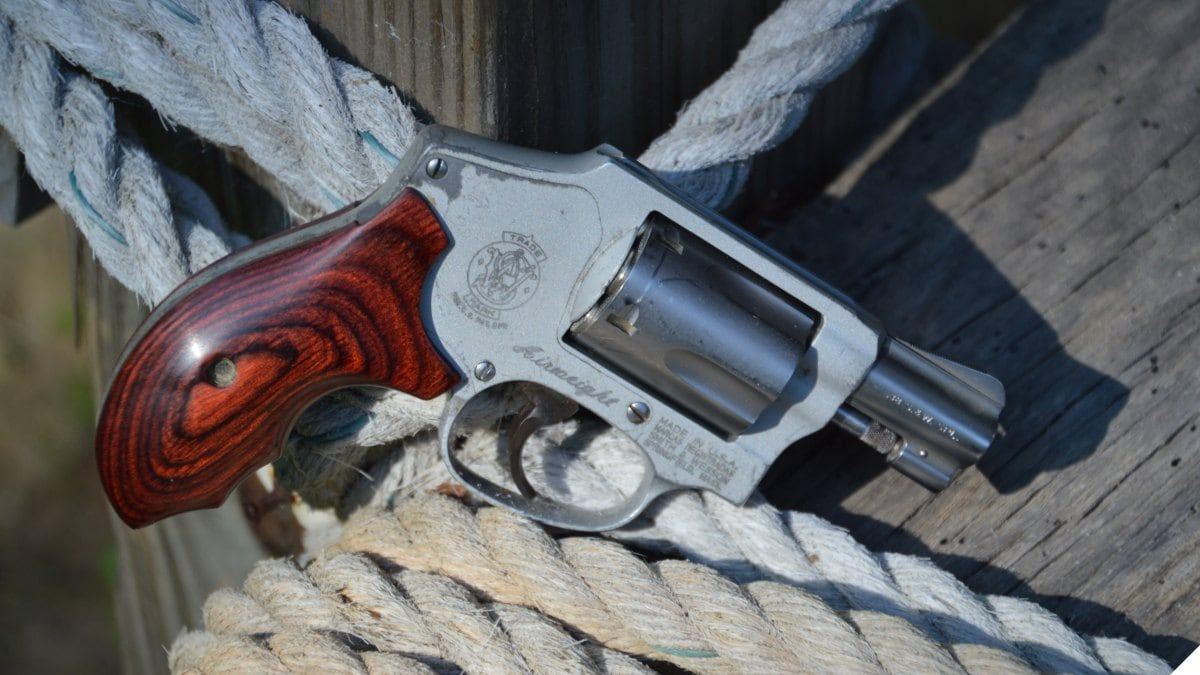 A Smith & Wesson Model 642 J-frame snub-nosed .38 Special revolver rests on a pile of rope atop a wooden bench.