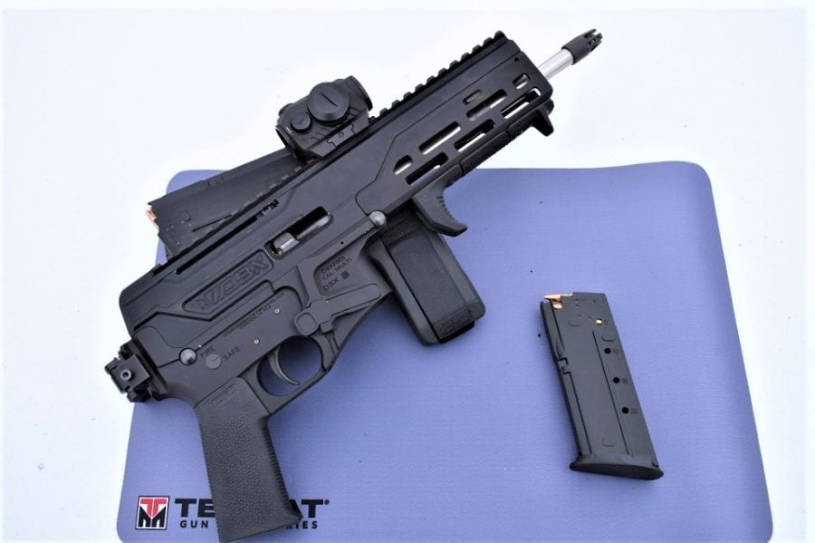 A table with a blue mat on top and a svelte Diamondback DBX 5.87x28mm pistol with folding brace and one FN Five-SeveN magazine